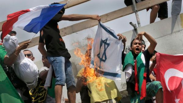 Pro-Palestinian protesters burn an Israeli flag during a demonstration against violence in the Gaza strip in Paris
